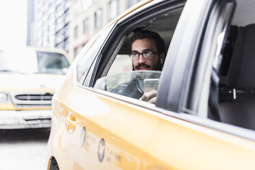 USA, New York City, businessman with cell phone and earphones in a taxi - UUF08977