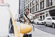 USA, New York City, smiling woman in Manhattan approaching a taxi - UUF08983