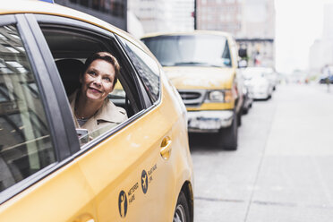 USA, New York City, smiling woman in taxi - UUF08986