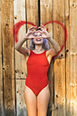 Portrait of young woman wearing red bodysuit in front of a heart - KKAF00007