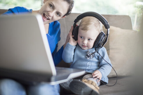 Mother with baby girl wearing headphones using laptop at home - ZEF11505