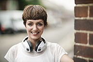 Portrait of happy young woman with short brown hair and white headphones - TAMF00764