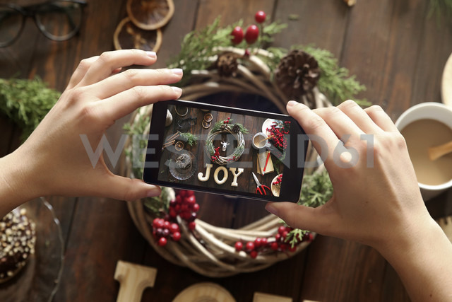 Woman's hands taking picture of self-made Advent wreath with smartphone - RTBF00487