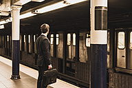 Young businessman waiting at metro station platform - UUF08995