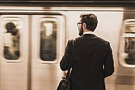 Young businessman waiting at metro station platform - UUF08998