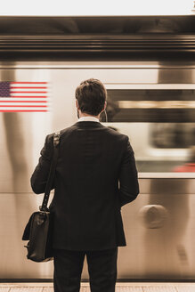 Young businessman waiting at metro station platform - UUF09001