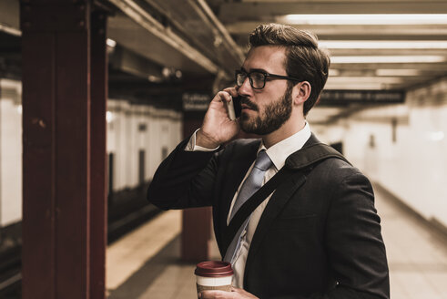 Young businessman waiting at metro station platform, using smart phone - UUF09007