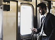 Young businessman taking metro, using smart phone - UUF09010