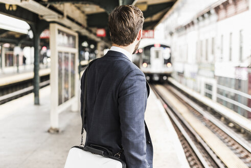 Young businessman waiting at metro station platform - UUF09019