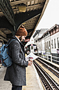 Young man waiting at metro station platform, reading documents - UUF09028