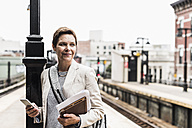 Mature woman using smart phone at commuter train station - UUF09040
