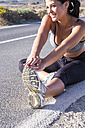 Young woman doing stretching exercises on an empty road - SIPF01026