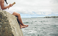 Barefoot woman sitting on pier reading a book, partial view - DAPF00460