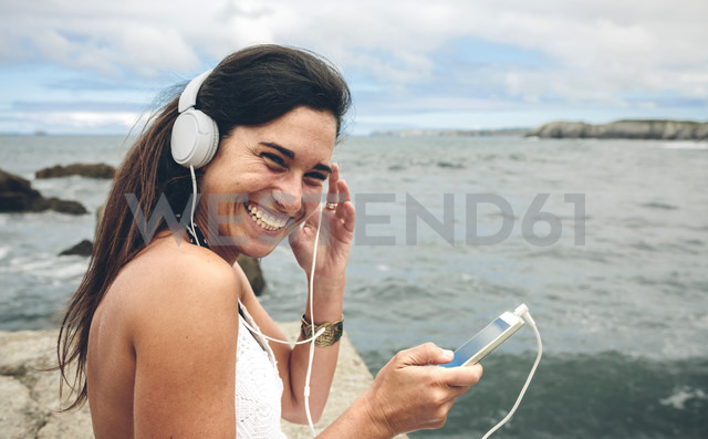 Laughing woman listening music with headphones in front of the sea - DAPF00463 - David Pereiras/Westend61