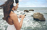Woman listening music with headphones and smartphone in front of the sea - DAPF00466