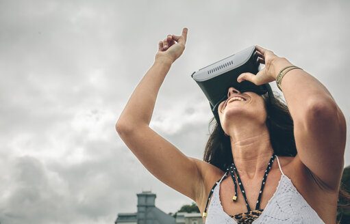 Smiling woman using Virtual Reality Glasses outdoors - DAPF00469