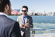 USA, New York City, two businessmen on ferry on East River - UUF09061
