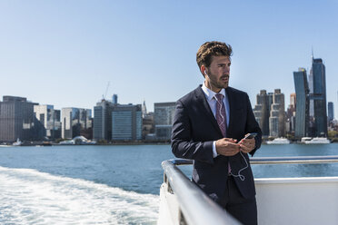 USA, New York City, businessman on ferry on East River with cell phone and earphones - UUF09064