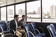 Two businessmen with document talking on passenger deck of a ferry - UUF09091