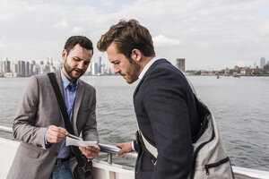 USA, New York City, two businessmen reviewing document on ferry on East River - UUF09097