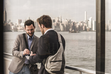 USA, New York City, two businessmen reviewing document on ferry on East River - UUF09103
