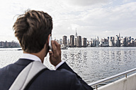 USA, New York City, back view of man on the phone with skyline of Manhattan in background - UUF09106