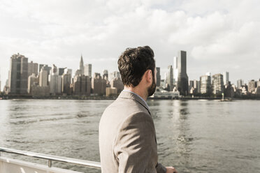 USA, New York City, back view of man at East River looking on Manhattan - UUF09115