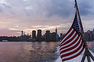 USA, New York City, US flag on ferry on East River with skyline of Manhattan in background - UUF09118