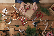 Woman's hands decorating Christmas present - RTBF00493