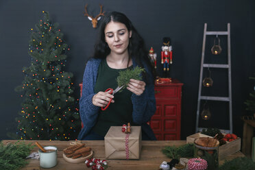 Young woman cutting twig for decorating Christmas present - RTBF00496