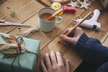 Woman writing on Christmas present tag, close-up - RTBF00511