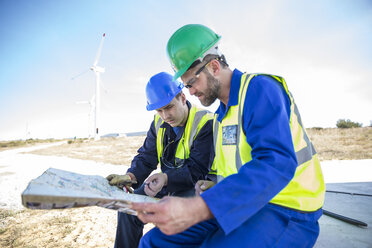 Engineers at wind farm looking at map - ZEF11514
