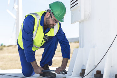 Engineer inspecting wind turbine, using wrench - ZEF11517
