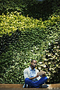 Young businessman using digital tablet in front of green plant wall - WESTF21893