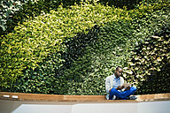 Young businessman using digital tablet in front of green plant wall - WESTF21896