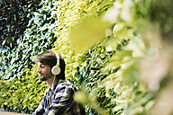 Young man sitting in front of green plant wall, wearing head phones - WESTF21908