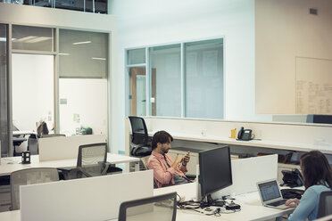People working in office, using mobile devices - WESTF21920