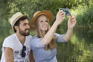 Smiling young couple at a lake taking a selfie - CRF02763