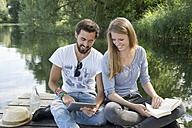 Smiling young couple sitting on jetty at a lake with book and tablet - CRF02766