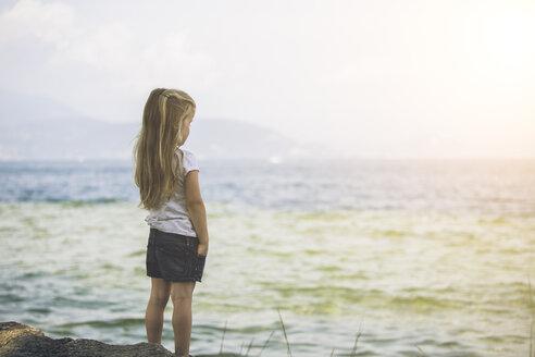 Italy, Lake Garda, girl standing at lakeshore - SBOF00256