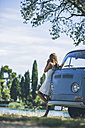 Italy, Lake Garda, young woman drinking coffee at camping bus - SBOF00262
