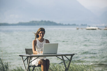 Italy, Lake Garda, young woman sitting at table with laptop - SBOF00265