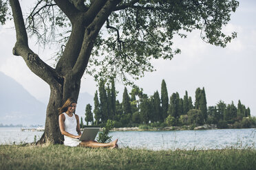 Italy, Lake Garda, young woman leaning against a tree using laptop - SBOF00268