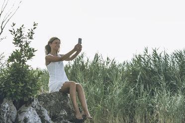 Italy, Lake Garda, young woman taking a selfie - SBOF00271