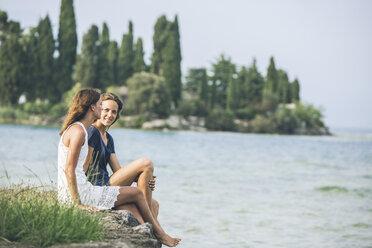 Italy, Lake Garda, two young women sitting at lakeshore - SBOF00274