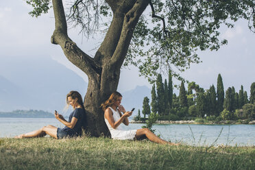 Italy, Lake Garda, two young women leaning against a tree using cell phones - SBOF00277