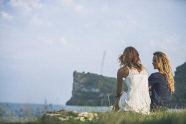 Italy, Lake Garda, two young women sitting at lakeshore - SBOF00280