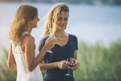 Italy, Lake Garda, two young women at lakeshore with glass of wine - SBOF00283