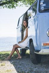 Italy, Lake Garda, smiling young woman in camping bus - SBOF00289