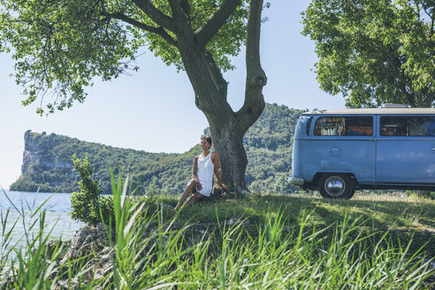 Italy, Lake Garda, woman sitting at camping bus at lakeshore - SBOF00295